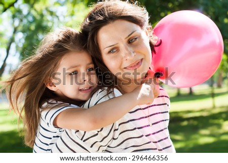 Portrait of Young Happy Beautiful Mother and Daughter with Pink Balloon. Hug in Sunny Day  - stock photo