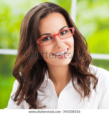 Portrait of young happy brunette businesswoman - stock photo
