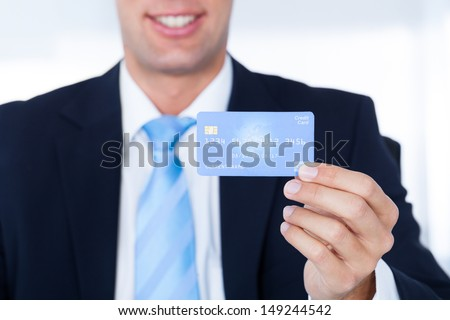 Portrait Of Young Happy Businessman Holding Credit Card - stock photo