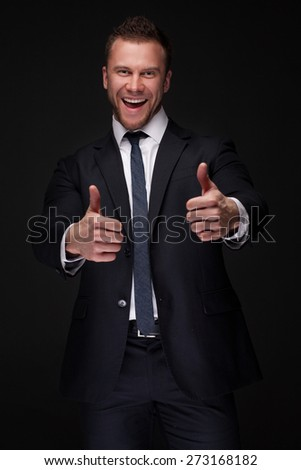 Portrait of young happy businessman with thumbs up isolated on dark background blending into background - stock photo