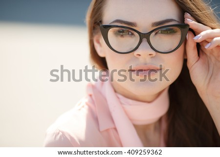 Portrait of young happy cheerful  woman in glasses outdoors - stock photo