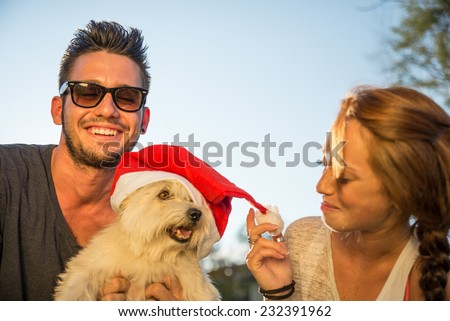 Portrait of young happy couple and dog with christmas hat - stock photo