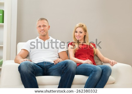 Portrait Of Young Happy Couple On Sofa  - stock photo