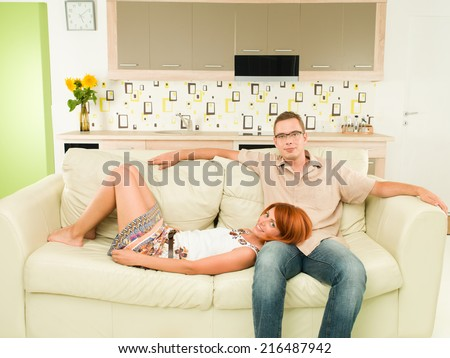 portrait of young happy couple sitting on sofa - stock photo