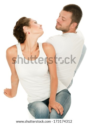 Portrait of young happy couple sitting on the floor, isolated on white background - stock photo