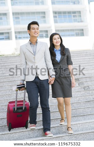 Portrait of young happy couple with baggage going to airport - stock photo