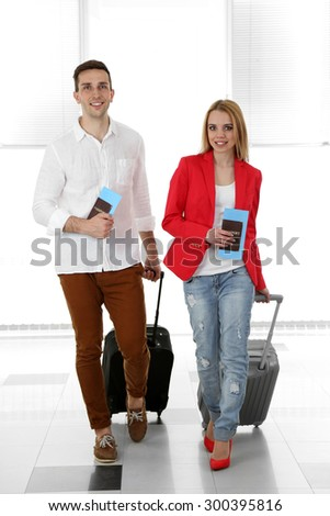 Portrait of young happy couple with baggage in airport