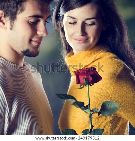 Portrait of young happy couple with red; rose, outdoor - stock photo