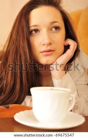 Portrait of young happy dreaming woman at home drinking coffee in the morning on weekend - stock photo