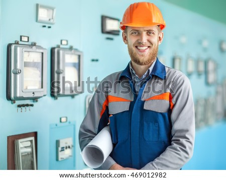 Portrait of young happy engineer in control room in factory