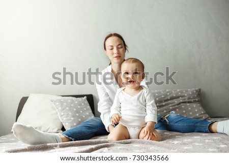 Portrait of young happy family of handsome mother and newborn son spending precious time together, smiling and playing in bedroom.