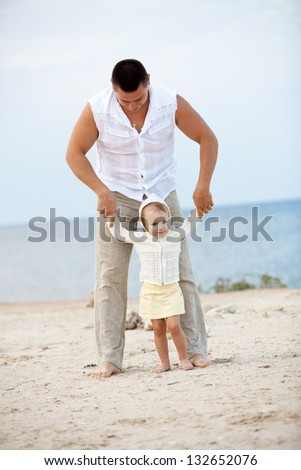 Portrait of young happy father playing with his child at the beach