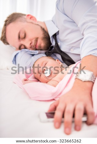Portrait of young happy father with a baby at home