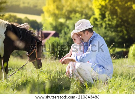 Portrait of young happy father with his dauhter at countryside outdoors, feeding pony - stock photo