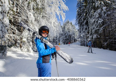 Portrait of young happy female skier on a ski slope in the winter forest on a sunny day. Girl is holding skis on her shoulder and looking towards the camera. Ski resort. Carpathian Mountains, Bukovel - stock photo