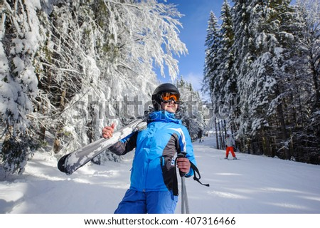Portrait of young happy female skier on a ski slope in the winter forest on a sunny day. Woman is holding skis on her shoulder. Ski resort. Carpathian Mountains, Bukovel, Ukraine - stock photo