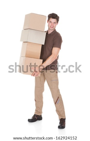 Portrait Of Young Happy Man Carrying Stack Of Boxes