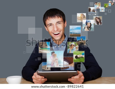 Portrait of young happy man sharing his photo and video files in social media resources using his modern tablet computer. Indoors - stock photo