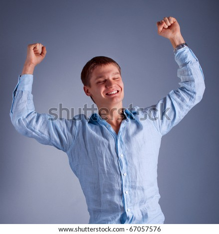 portrait of young happy man with raised hands - stock photo