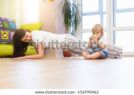 Portrait of young happy mother doing fitness exercise at home and having fun with her baby boy near a window
