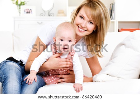 Portrait of young happy mother with newborn baby at home - stock photo