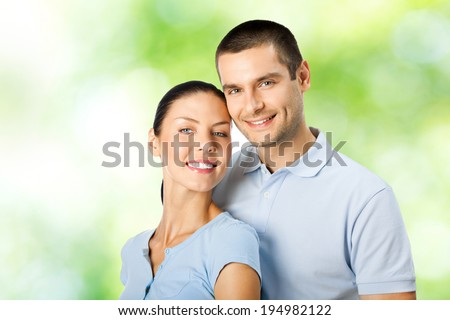 Portrait of young happy smiling attractive amorous couple, outdoors - stock photo