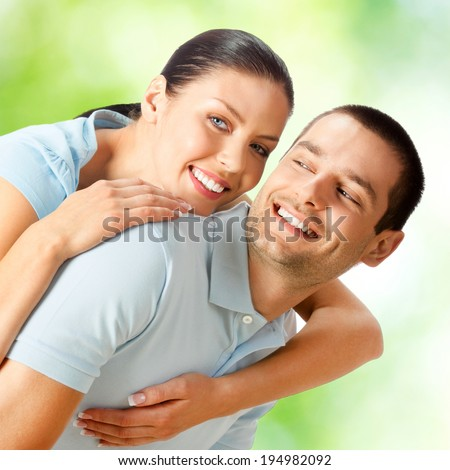 Portrait of young happy smiling attractive amorous embracing couple, outdoors