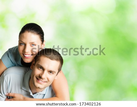 Portrait of young happy smiling attractive couple outdoors, with copyspace - stock photo