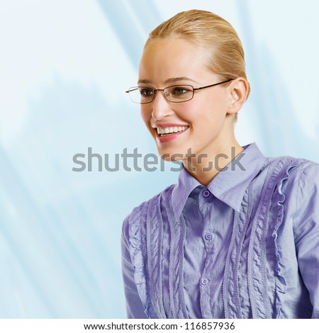 Portrait of young happy smiling blond business woman, at office - stock photo