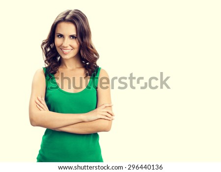 Portrait of young happy smiling brunette woman in smart green casual clothing, with crossed arms, with blank copyspace area for slogan or text - stock photo