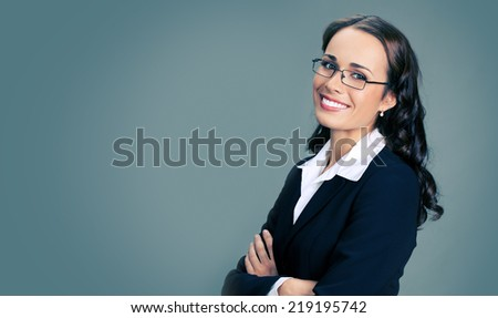 Portrait of young happy smiling business woman in glasses, over gray background, with copyspace - stock photo