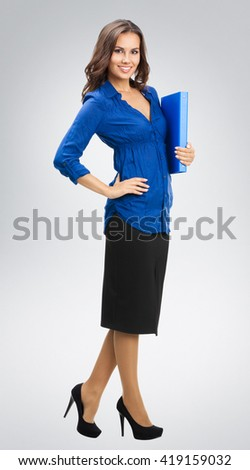 Portrait of young happy smiling businesswoman with blue folder, against grey background - stock photo