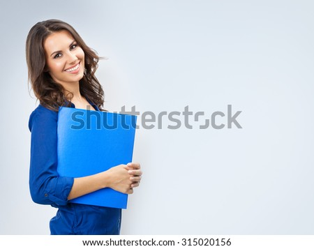 Portrait of young happy smiling businesswoman with blue folder, with blank copyspace area for slogan or text, posing at studio - stock photo