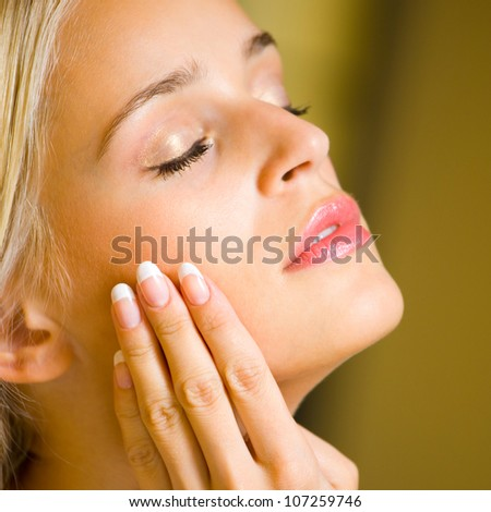 Portrait of young happy smiling cheerful beautiful blond woman applying creme, at home