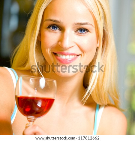 Portrait of young happy smiling cheerful beautiful blond woman with redwine - stock photo