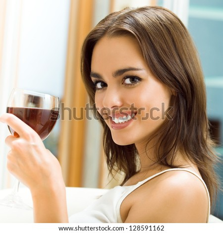 Portrait of young happy smiling cheerful beautiful woman with glass of red wine - stock photo
