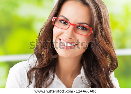 Portrait of young happy smiling cheerful business woman in glasses, at office - stock photo