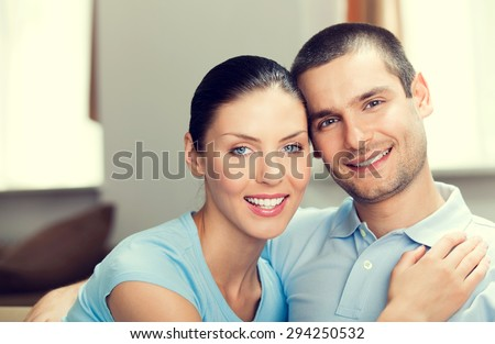 portrait of young happy smiling lovely couple in blue casual smart clothing, indoor - stock photo