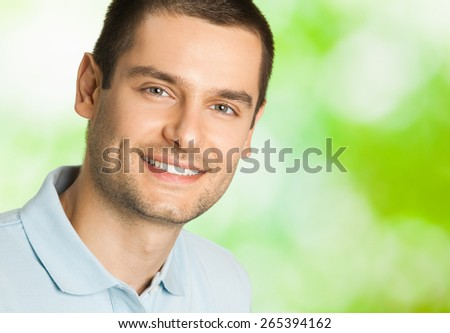 Portrait of young happy smiling man, outdoors, with copyspace area for text or slogan - stock photo