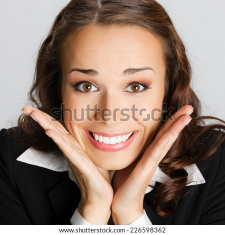 Portrait of young happy smiling surprised business woman, against grey background - stock photo