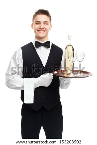 Portrait of young happy smiling waiter with bottle of white wine and stemware glass on tray isolated on white background