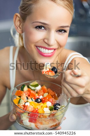 Portrait of young happy smiling woman eating salad at home. Healthy eating and diet theme concept.