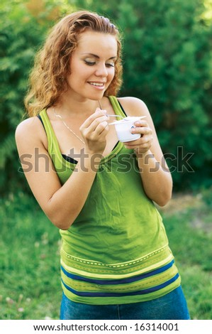 Portrait of young happy smiling woman eating yogurt - stock photo