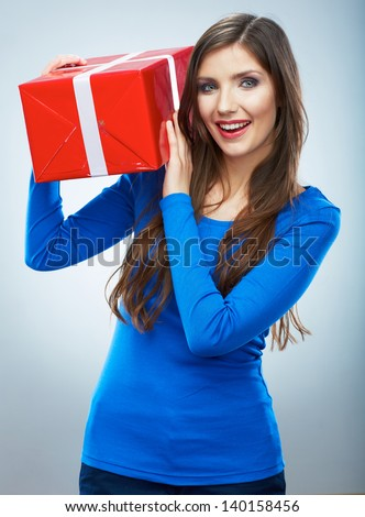 Portrait of young happy smiling woman hold red gift box. Isolated studio background female model. - stock photo