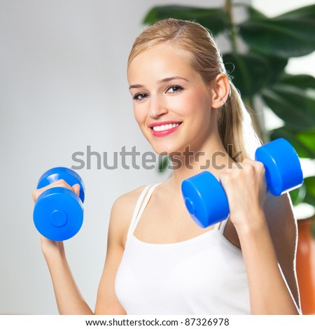 Portrait of young happy smiling woman in sportswear, doing fitness exercise with dumbbells, at home