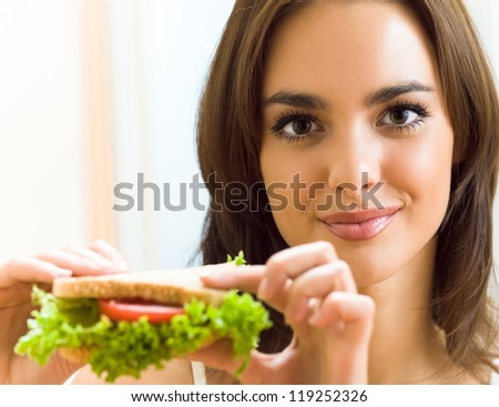 Portrait of young happy smiling woman with sandwich at home - stock photo