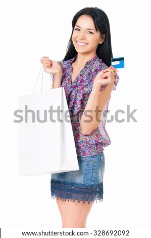 Portrait of young happy smiling woman with shopping bags showing credit card or gift card, isolated over white background