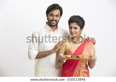Portrait of young happy south Indian couple, holding cookies and sweets for Indian festival on white. - stock photo