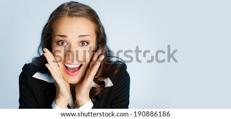 Portrait of young happy surprised business woman, over blue background - stock photo