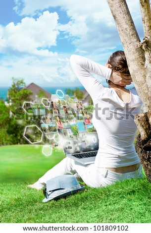 Portrait of young happy woman sharing her photo and video files in social media resources using her modern laptop. Outdoors at beautiful idyllic place. - stock photo